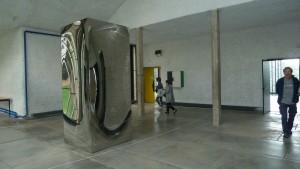 Dès l'entrée, Non object, un miroir vertical en acier inox accueille le visiteur et entre dans le jeu des reflets qui est un des traits de l'exposition (© Pierre Nouvelle).