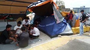 Sur le port du Pirée, des jeunes par centaines attendent. Ils tuent le temps, par exemple en jouant aux cartes (© Pierre Nouvelle).